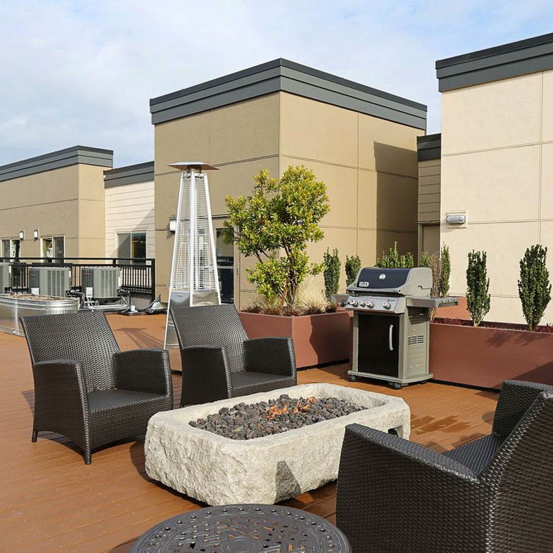 Outdoor Lounge area with fire pit and grill at Lake City Way Senior Housing