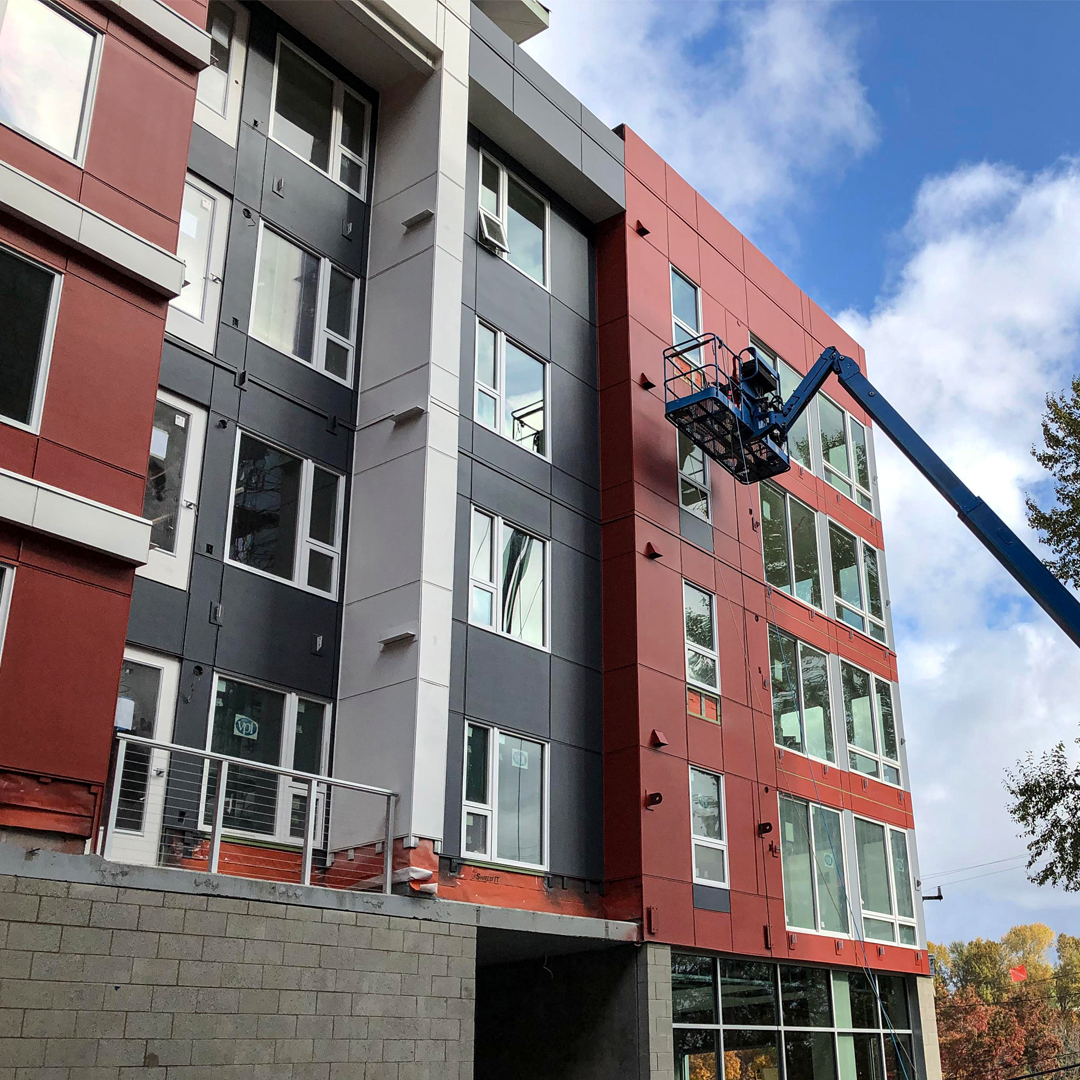 Worker on construction lift at Mt. Baker Station Apartments building